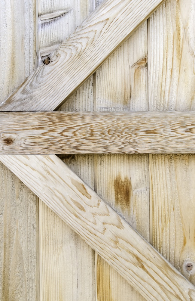 Reinforcing planks in the shape of an arrow across plain wooden fence-1.jpeg