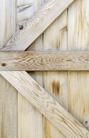 Reinforcing planks in the shape of an arrow across plain wooden fence-1.jpeg